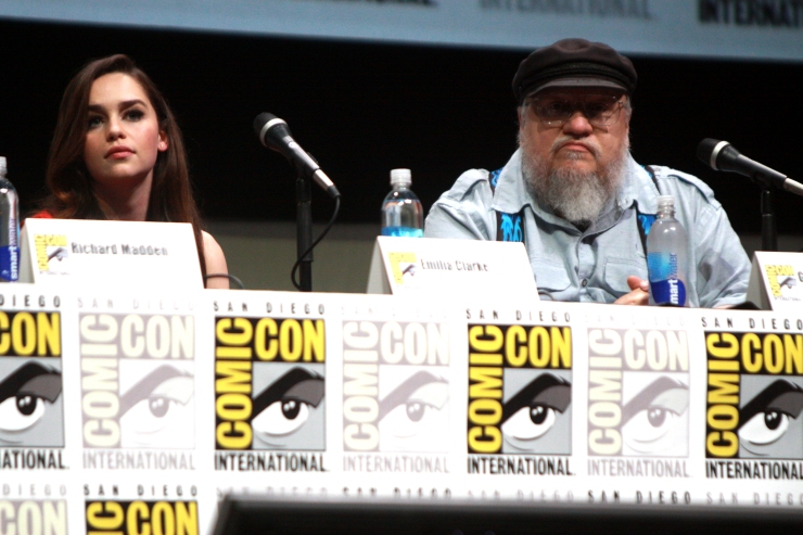 Emilia Clarke and George R.R. Martin at San Diego Comic Con. Emilia Clarke plays Daenerys Targaryen in Game of Thrones, a drama series based on Martin's book series